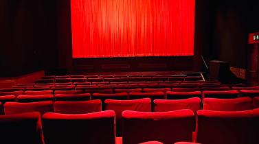 Empty theater with red seats and a red curtain
