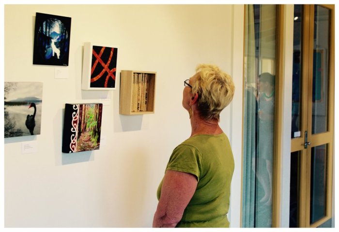 Pictured here is one lady looking through art pieces hung on the wall.