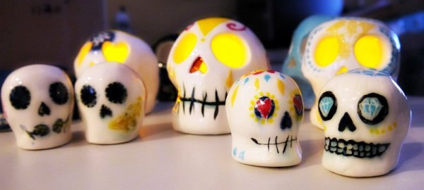 Picture shows six sugar skulls with differing sizes, painted in the style of El Dia de los Muertos.