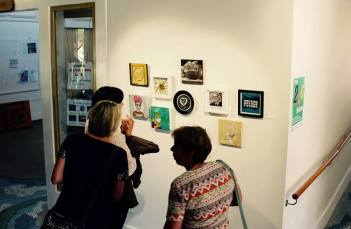 Pictured here are three ladies looking at a wall where art pieces are hung.