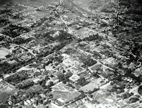 Even in 1929, Santa Fe was an art center, the state capital, and a historic community. It was still a town rather than a city, however, and agricultural fields can be seen not far from the Plaza (approximately at the center of the photo), the heart of the social and economic life of the town. The old capitol building can be seen surrounded by trees in the upper center. Trees also mark the Santa Fe River, which forms a wandering diagonal from lower left to upper right. North is to the right in this photograph. Photograph by Charles A. and Anne Morrow Lindbergh, 1929.