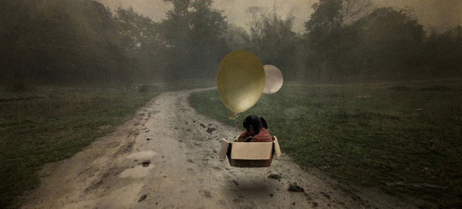 Person flying through landscape in cardboard box with balloons