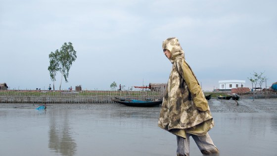 woman wading in water wearing portable shelter jacket