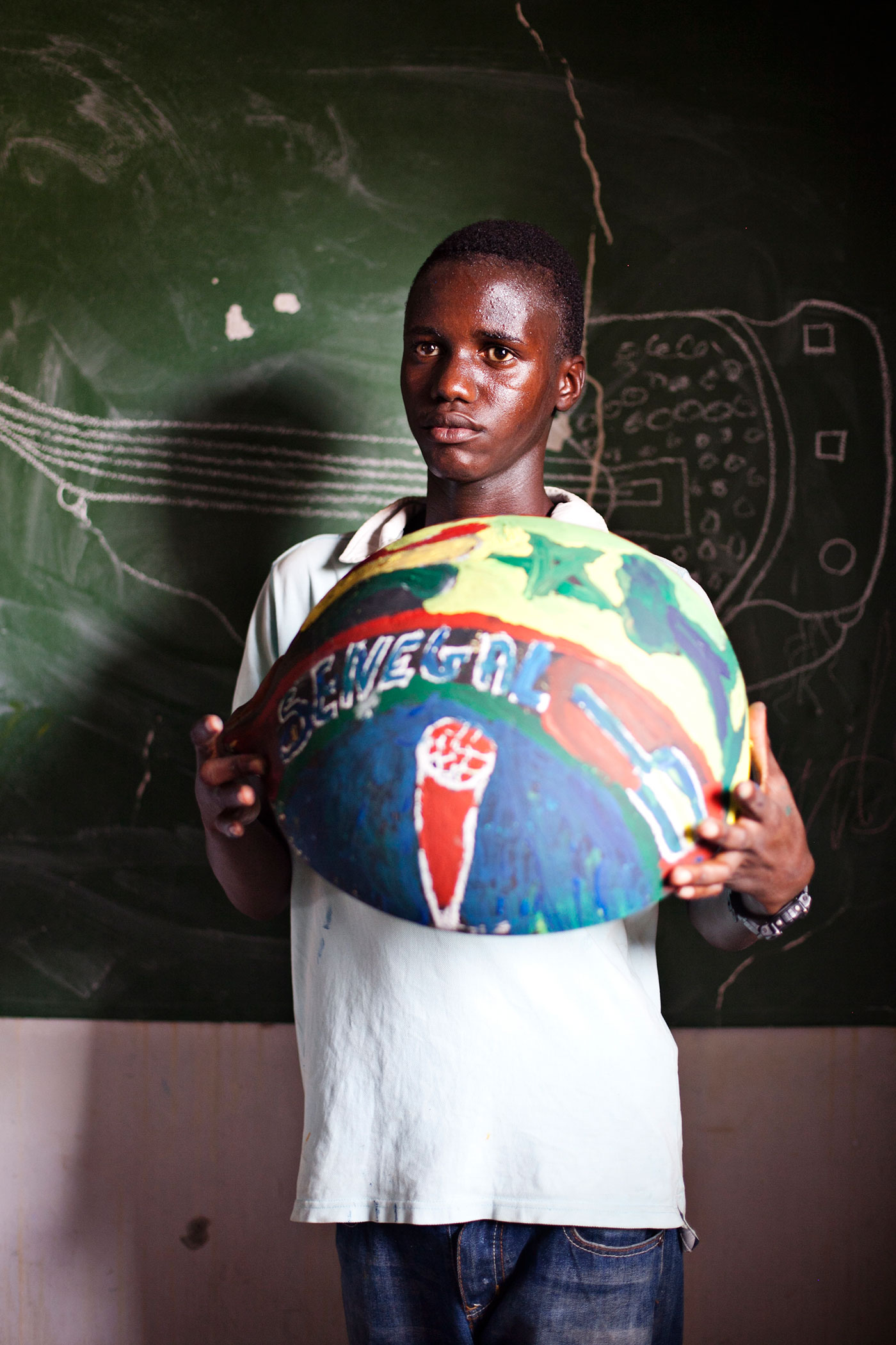 boy from Senegal holding painted bowl