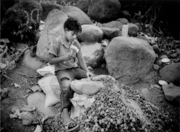 """Nino Picapedrero"" (child who dig out stones), sits for hours manually shatters rocks into gravel to earn money for his family. Guatemalan-American NGO CEIPA provides aid and education for underprivileged children such as these. Retalhuleu Province, Guatemala / 2010"