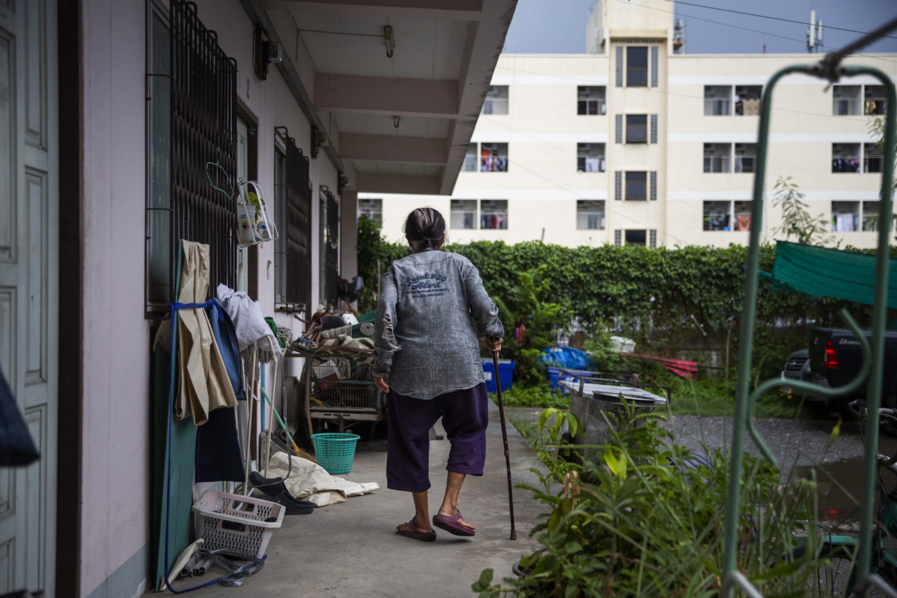 A person leaning on a cane walks outside their home.