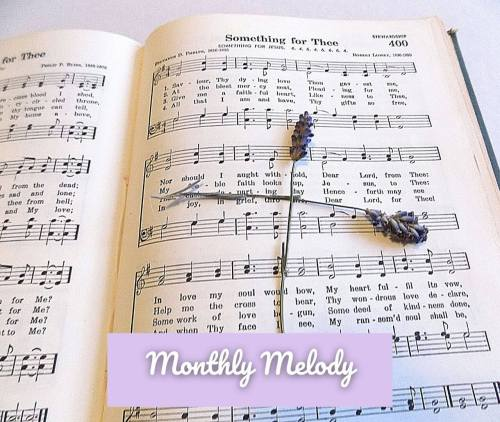 Hymn book with lavender in the shape of a cross labeled Monthly Melody