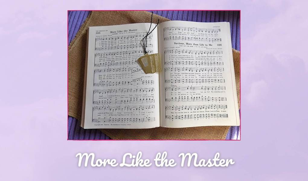 Hymn book on purple and burlap background with gold accordion bookmark. Hymn book is open to More Like the Master.