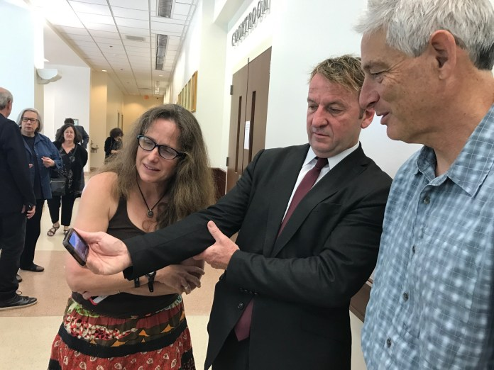 Gavin Buckley (center), Annapolis restauranteur and co-defendant in the City lawsuit against a mural on his West St. establishment, shows supporters a time-lapse video of the mural being painted in 2015.