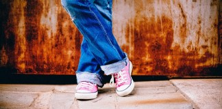 photo of a girls legs wearing cuffed jeans pink sneekers