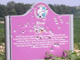 Emmett Till sign is a pink sign made of metal that has been shot through with numerous bullet holes.