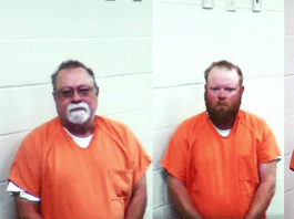 Two white men with beards in orange jumpsuits in jail.