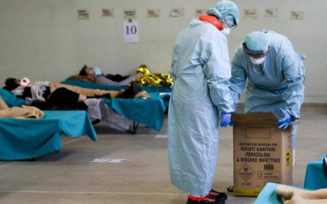 Paramedics carry an hazardous medical waste box as patients lie on camping beds, in one of the emergency structures that were set up to ease procedures at the Brescia hospital, northern Italy, Thursday, March 12, 2020. Italians woke up to yet further virus-containment restrictions after Premier Giuseppe Conte ordered restaurants, cafes and retail shops closed after imposing a nationwide lockdown on personal movement. For most people, the new coronavirus causes only mild or moderate symptoms, such as fever and cough. For some, especially older adults and people with existing health problems, it can cause more severe illness, including pneumonia. (AP Photo/Luca Bruno)