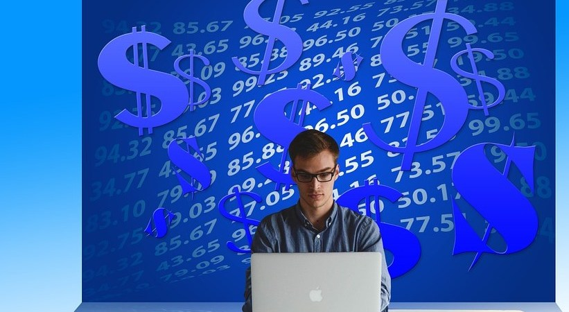 man working on a laptop with dollar icons on background