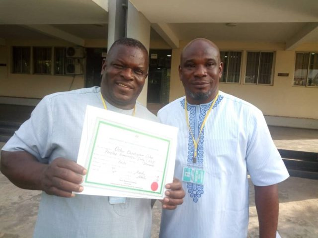 Hon Christopher Ochor Ochor, displaying His Certificate of return and Hon Sunday Onoriode, the Organising Secretary of the Delta State PDP at the INEC headquarters, Abuja.