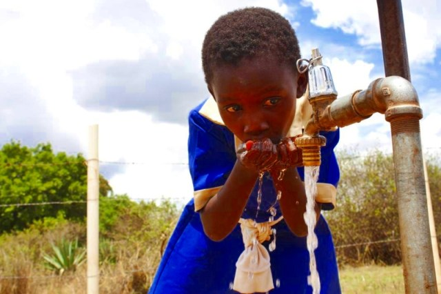 African School Girl Drinking Water From Public Tap