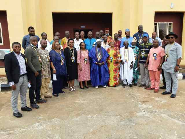 Management of NGC in a group photograph with members of Oben Community after the Commissioning aid handover of the civic Centre built by NGC for the community.