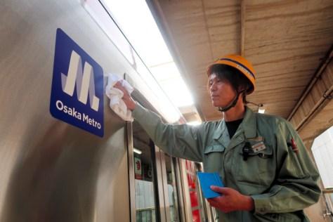 4月1日の始発列車となる御堂筋線の車両に新しいロゴマークを貼り付ける職員=3月31日午後、堺市北区の中百舌鳥検車場、左古将規撮影