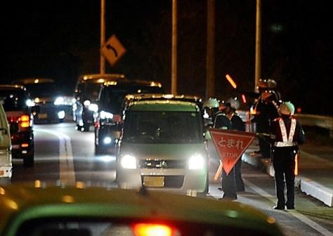 尾道大橋南詰めで、市中心部方面へ向かう車を検問する警察官=11日夜、広島県尾道市向東町(画像の一部を加工しています)