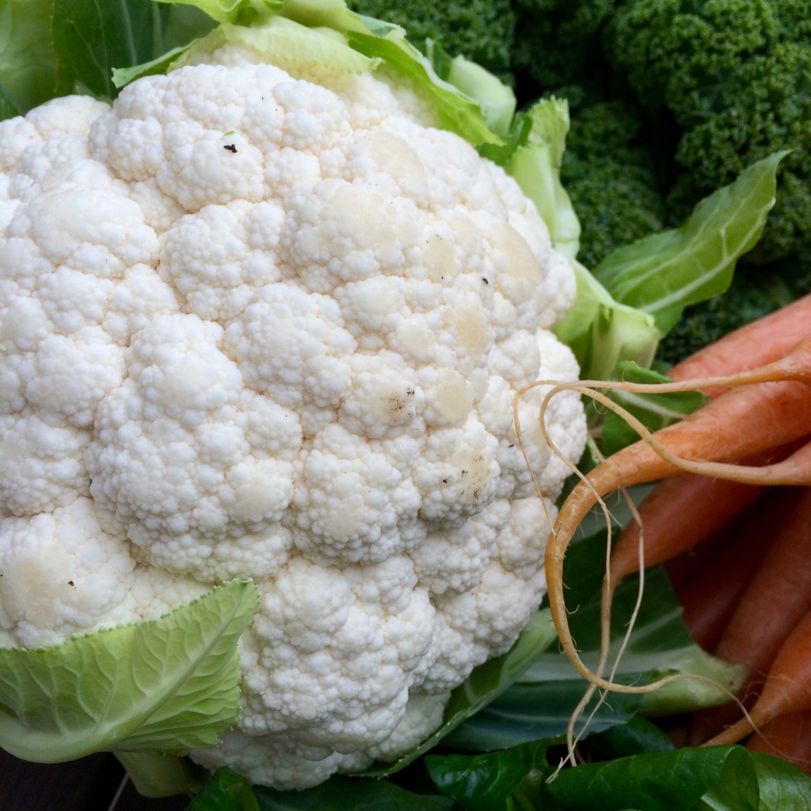A whole raw cauliflower next to some carrots
