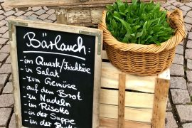 A basket of wild garlic and a chalkboard in German with serving suggestions
