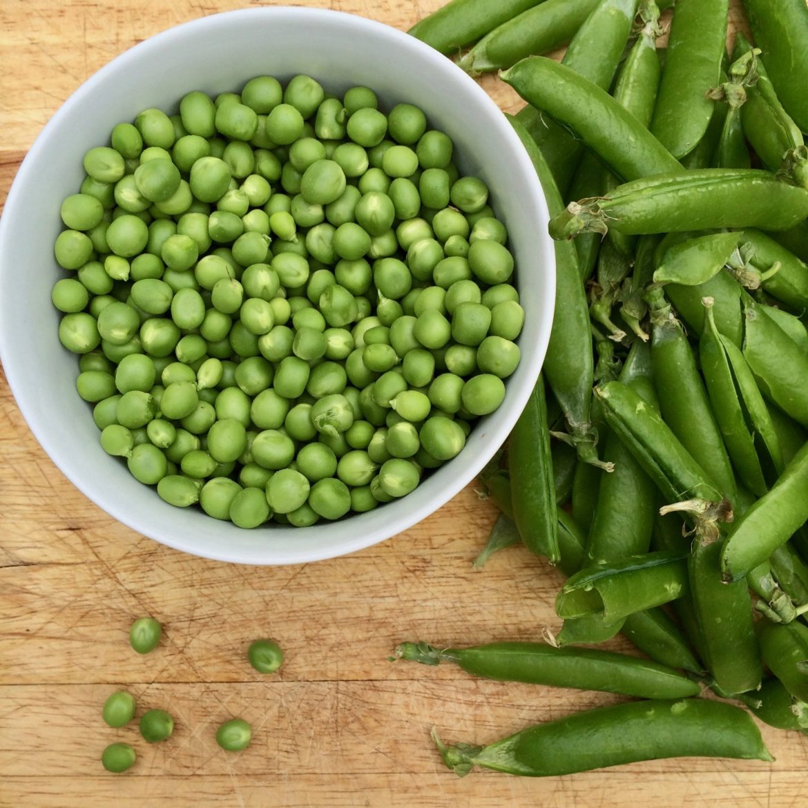 A bowl of fresh peas next to their pods