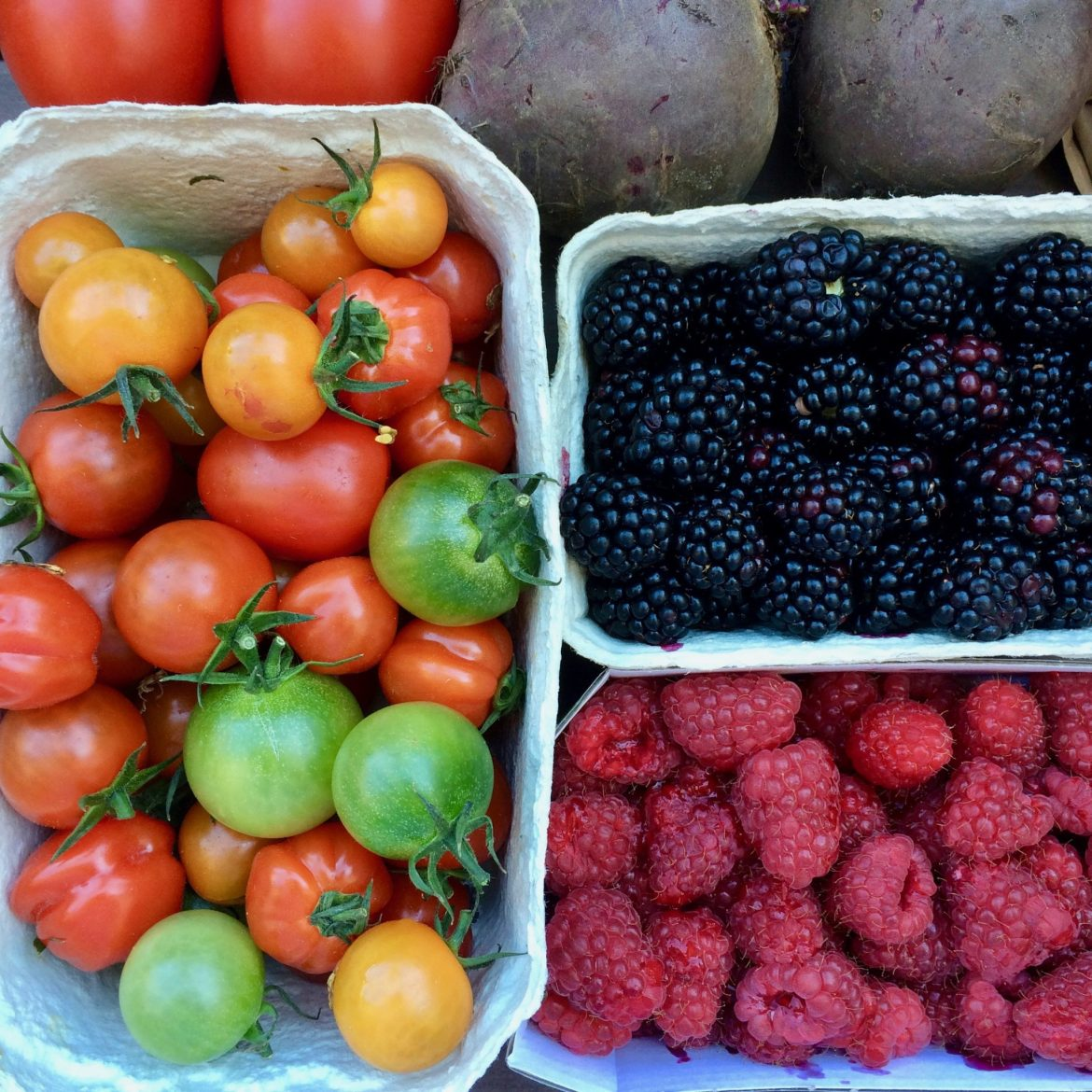 Flat lay of August fruit and vegetables: tomatoes, raspberries, blackberries and beetroot