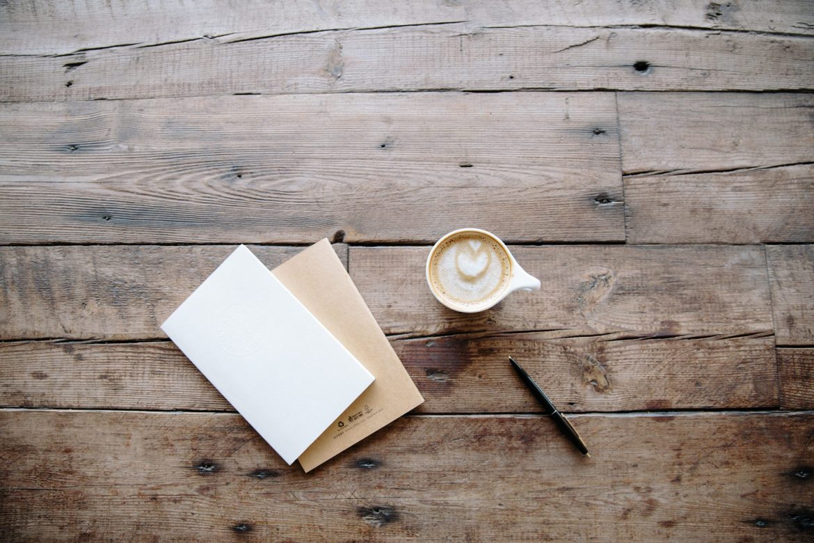 Books, coffee and a pen on a wooden table