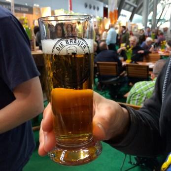 A glass of German beer being held at a tasting