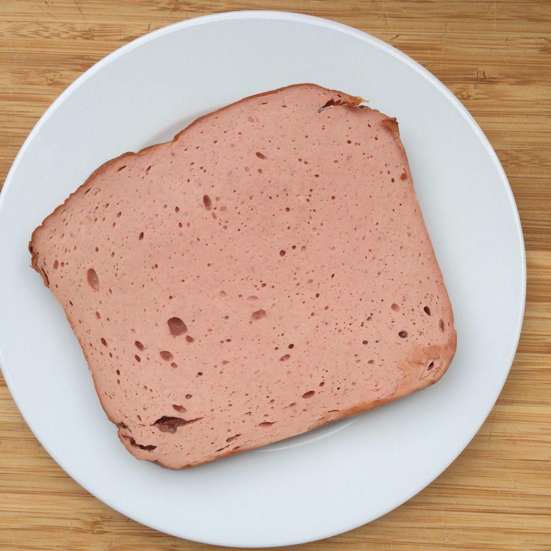 A slice of Leberkäse on a plate