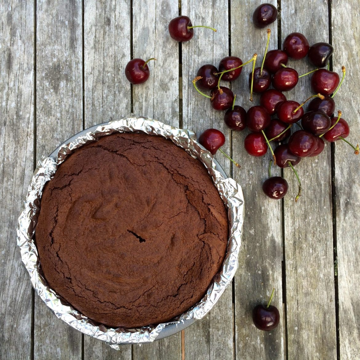 A tray of cooked brownie with fresh cherries