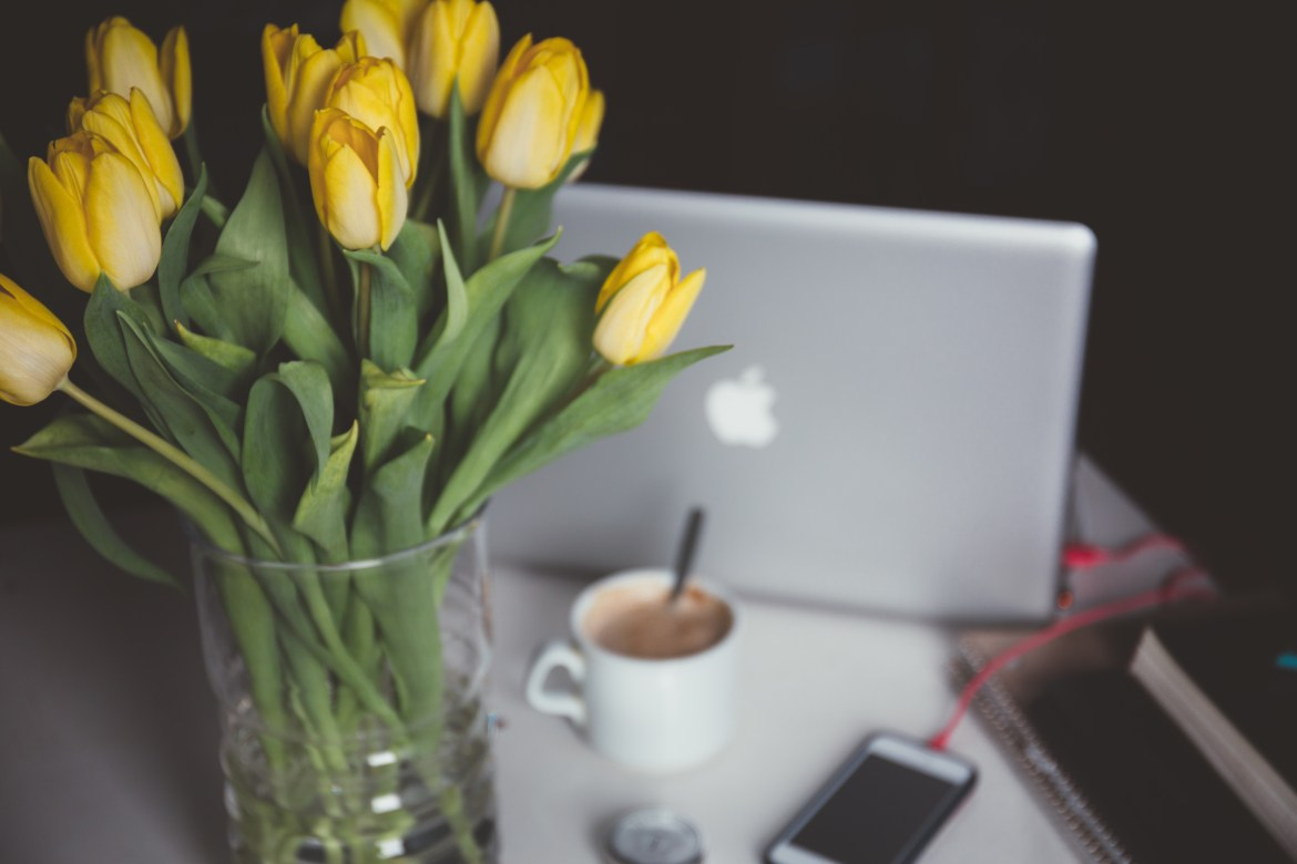 Yellow tulips, a mug of coffee and a laptop