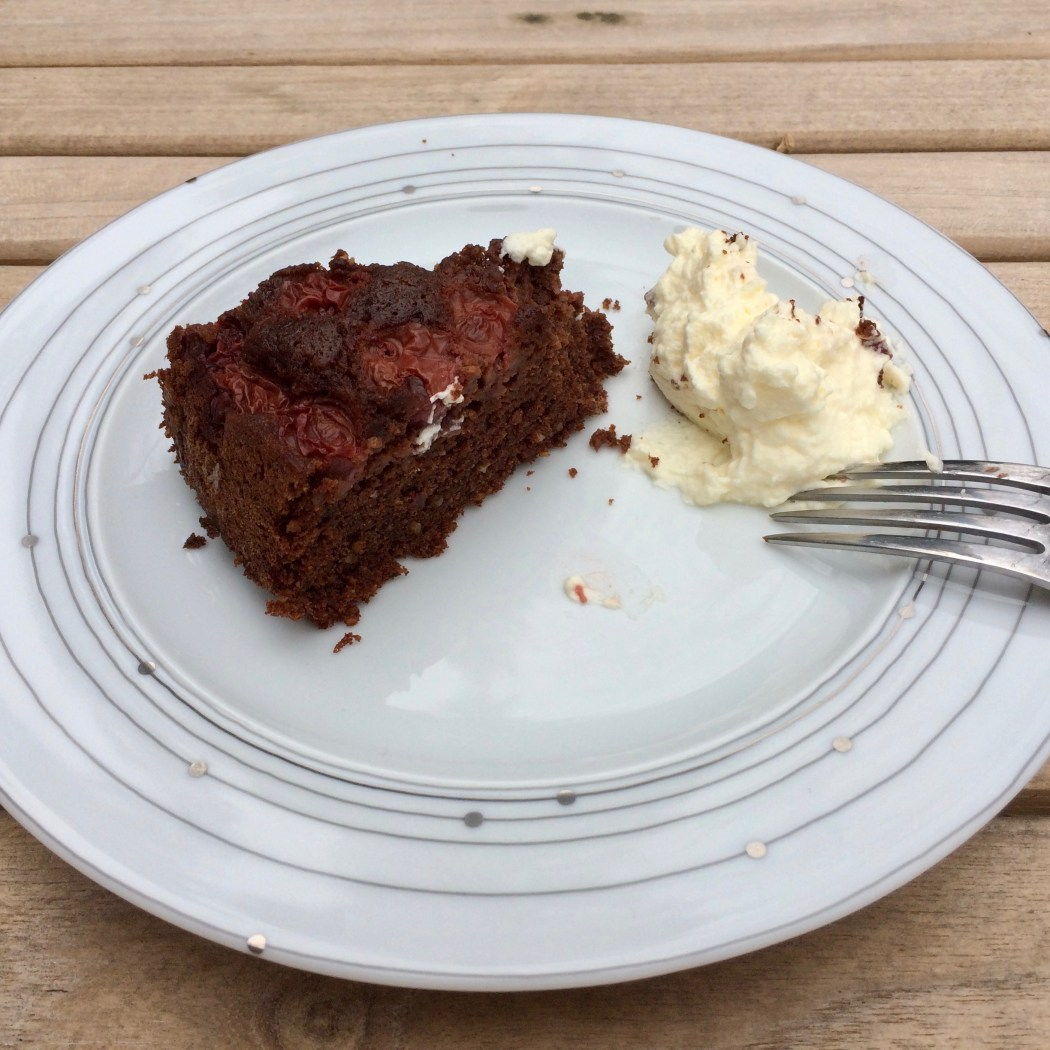 A slice of dark chocolate cherry cake with plate and fork