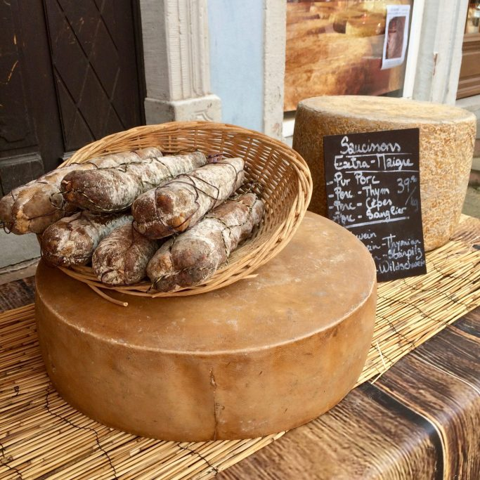 A wooden bowl of French cured sausage on a large round cheese