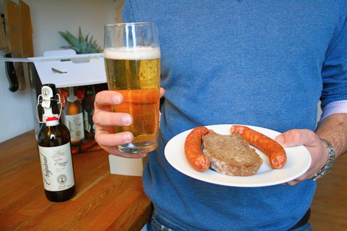 Man holding a tall glass of Export beer and sausages with bread on a plate