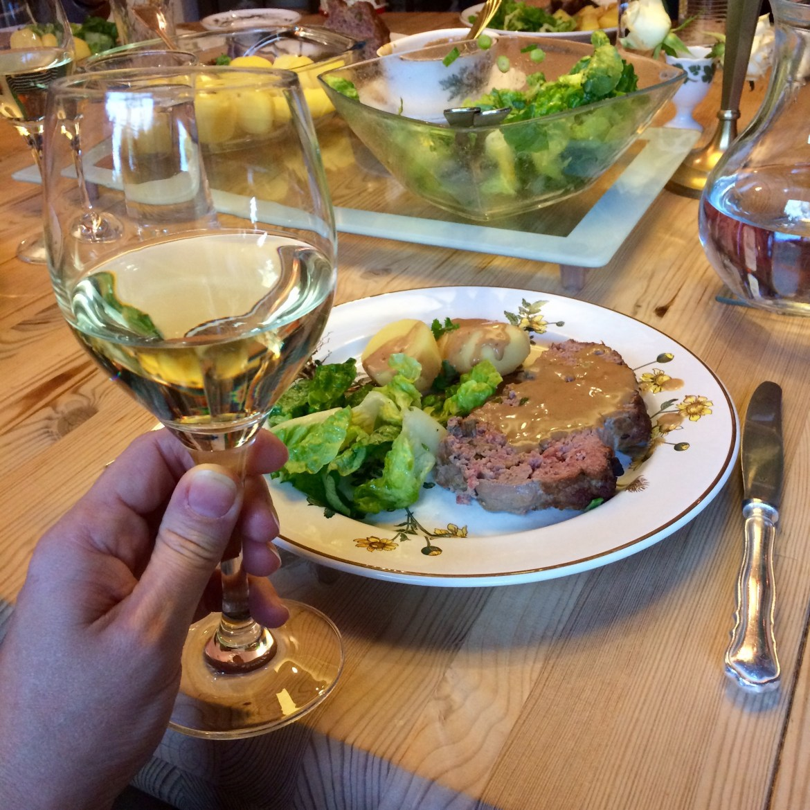 A glass of Riesling being held in front of a plate of German meatloaf, potatoes and salad