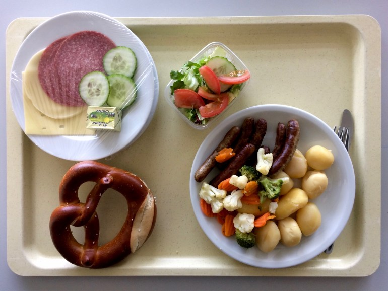 A tray of sausages and potatoes and a pretzel from above