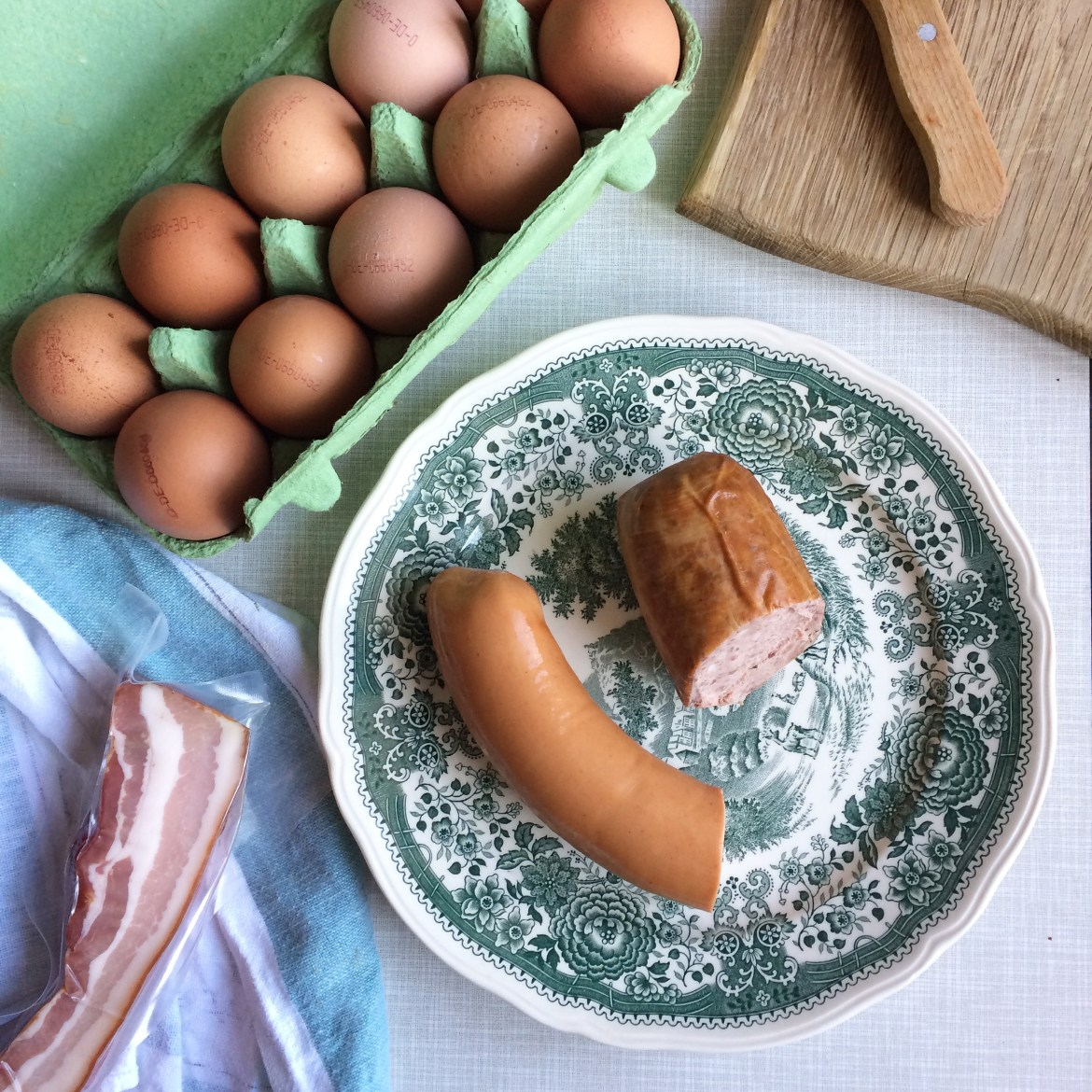 A green patterned plate with Fleischwurst and Leberwurst on next to a carton of eggs and some vacuum-packed bacon
