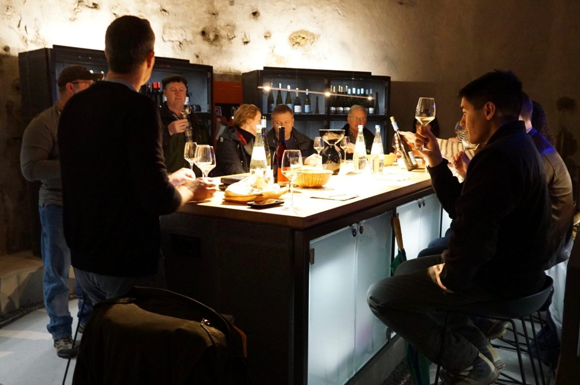 A group of people tasting wine around a tall table in a dark cellar