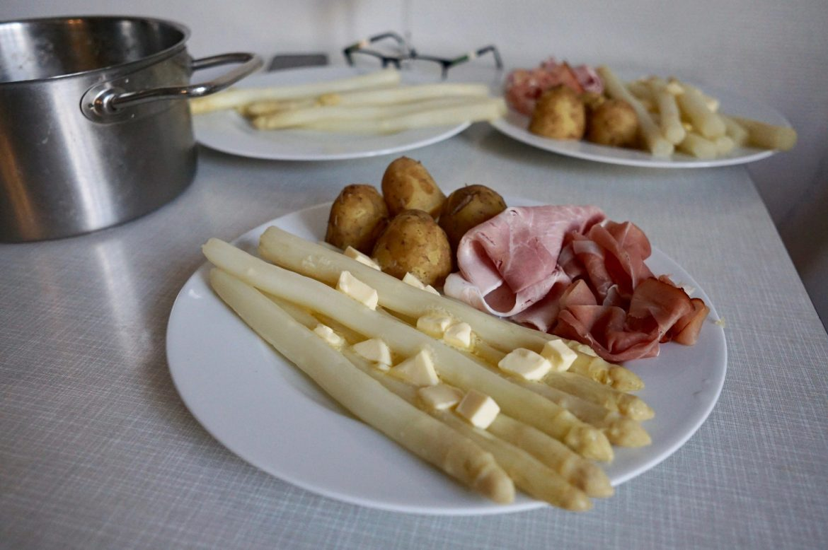 White asparagus with new potatoes and two kinds of ham on a white plate