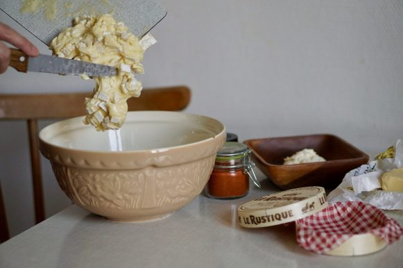 Chopped Camembert sliding off a board into a large bowl