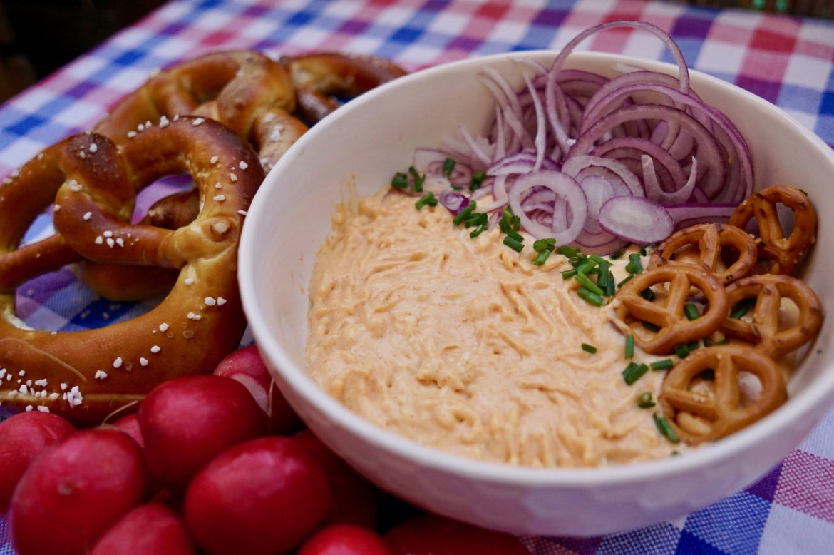 Obatzda in a bowl with pretzels, onion and chives, and radishes on the side