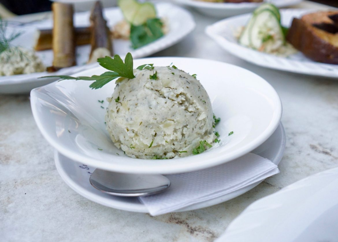 A white bowl with a ball of Fischtüfte in, garnished with parsley