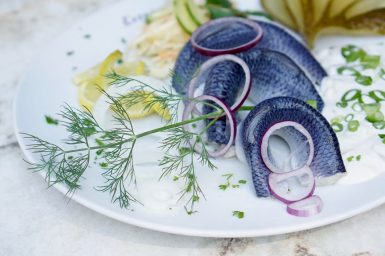 Close up of a white plate of vinegar-marinated herring with dill and red onion