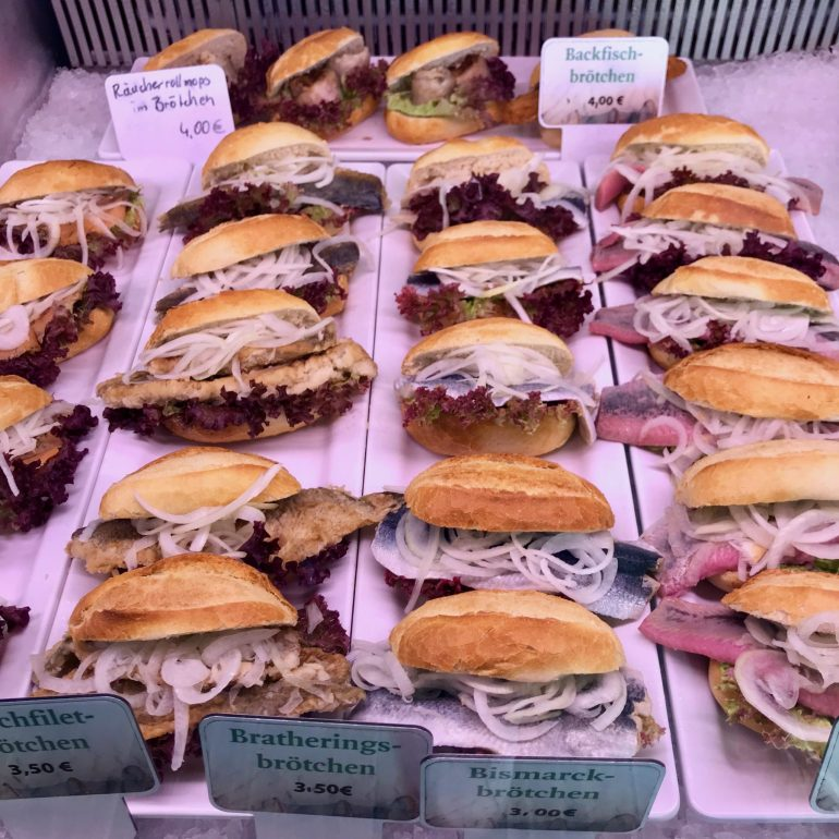 A selection of fish sandwiches under a glass counter