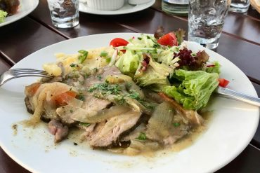 A white plate with pork and onions, potato salad and green salad on a wooden table