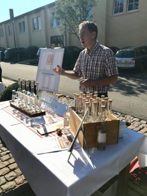 Man in front of a display of bottles of fruit brandies