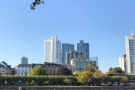 Riverbank in Frankfurt with a sunny view of skyscrapers and people