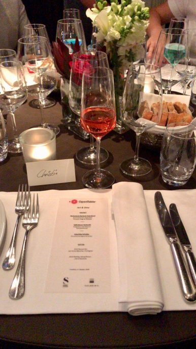 A table laid with cutlery and glasses and a menu