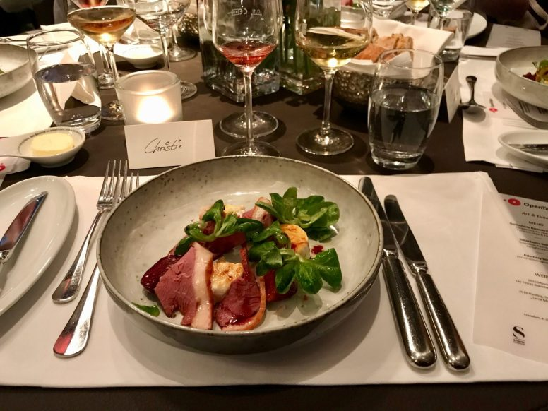 Smoked duck with goat's cheese, figs and lamb's lettuce on a plate on a restaurant dining table
